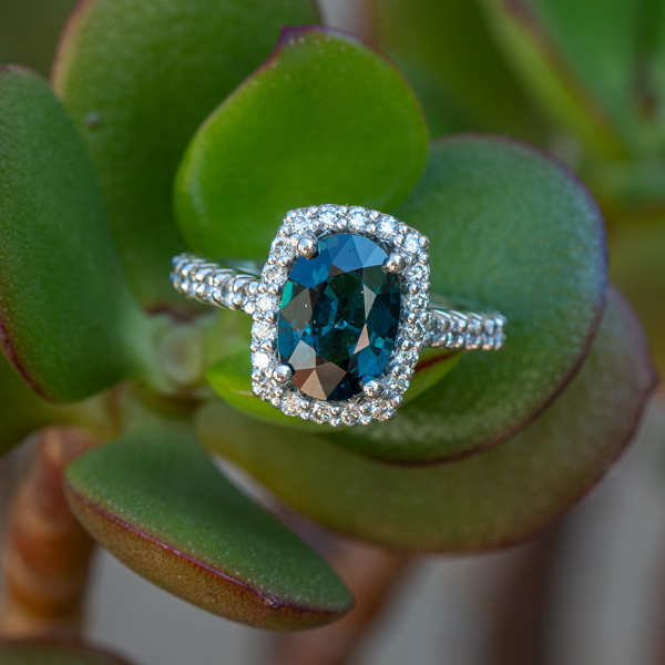 Oval peacock sapphire and diamond halo engagement ring